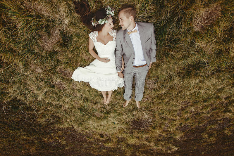 Jeune mariée magnifique et marié élégant se trouvant sur le dessus, cou de mariage de boho photo libre de droits