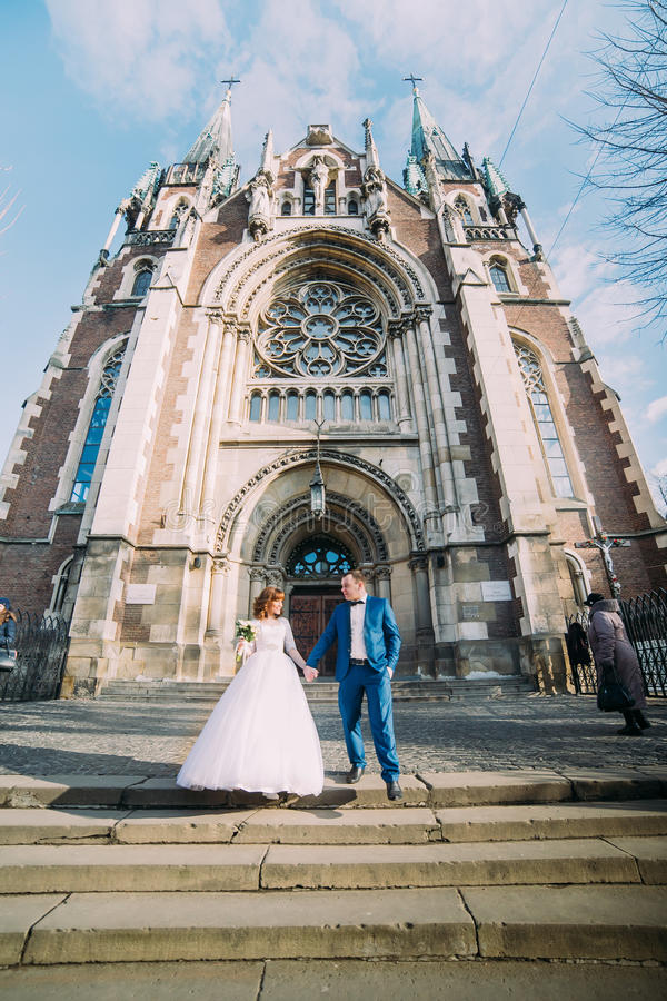 Jeune mariée magnifique heureuse et marié beau élégant se tenant tenants des mains sur le fond d'une église étonnante de bâtiment image stock
