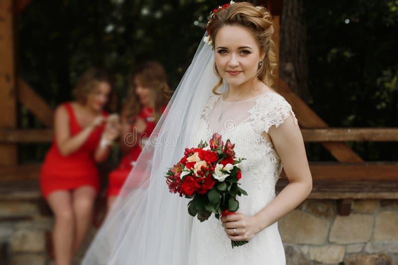 Jeune mariée magnifique souriant et posant avec le bouquet de mariage dehors photographie stock
