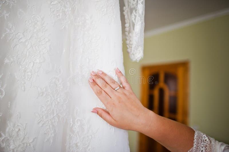 Jeune mariée magnifique touchant sa robe de mariage avant le CER l'épousant image stock