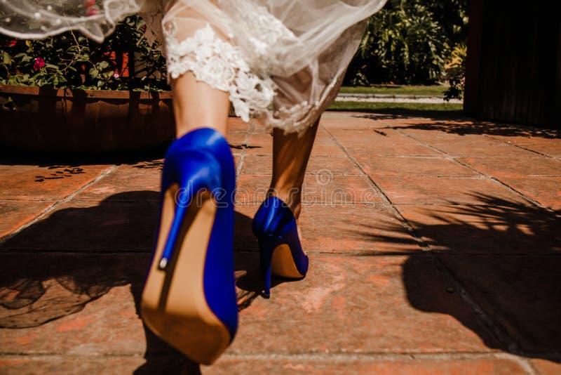 Jeune mariée marchant avec les chaussures bleues de talon haut photos libres de droits