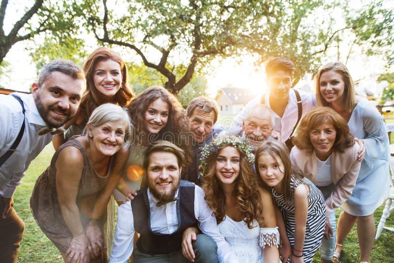 Jeune mariée, marié, invités posant pour la photo à la réception de mariage dehors dans l'arrière-cour image stock