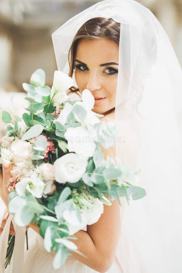 Jeune mariée merveilleuse avec une robe et un bouquet blancs luxueux photographie stock