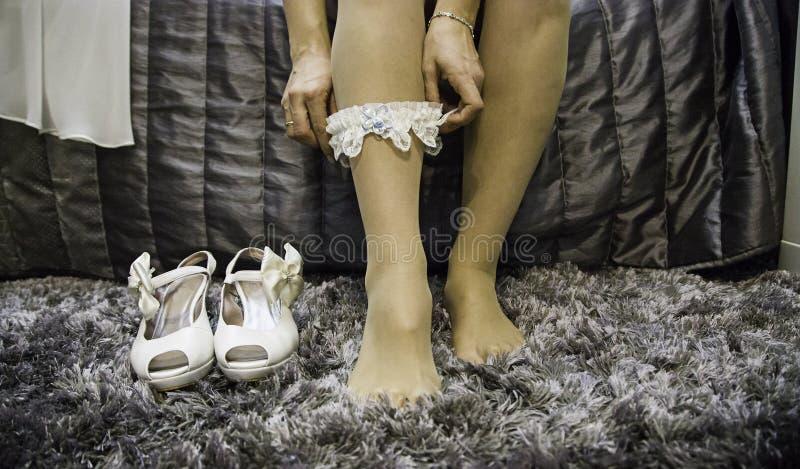 Jeune mariée mettant sur des bas photo libre de droits
