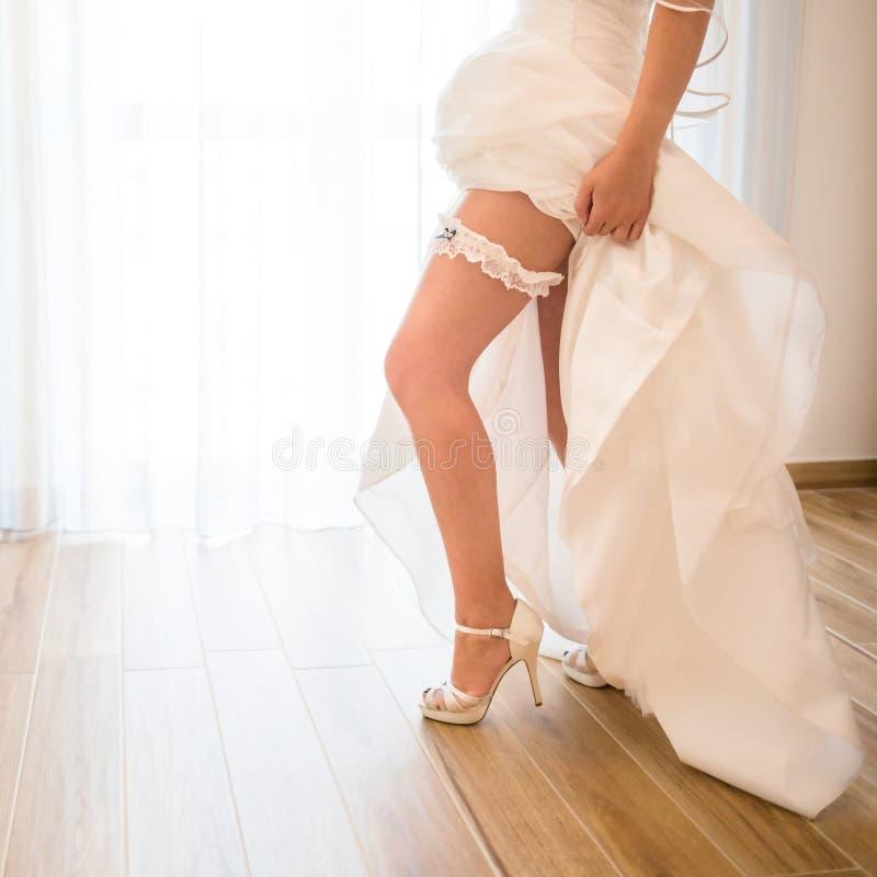 Jeune mariée mettant sur la jarretière de mariage image libre de droits