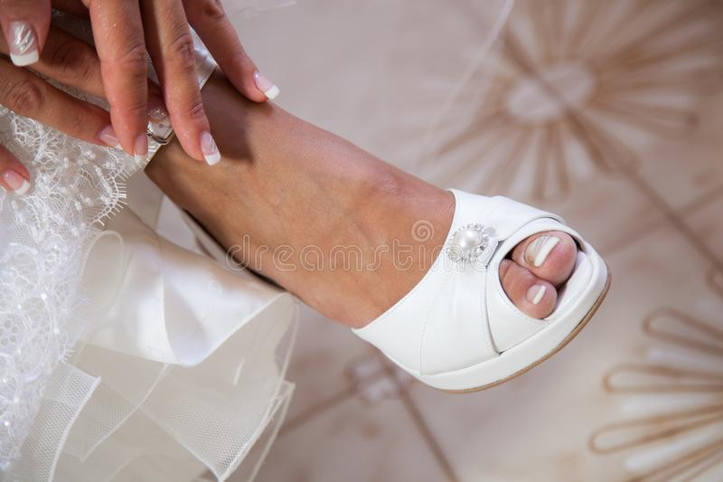 Jeune mariée mettant sur ses chaussures blanches de mariage photos stock