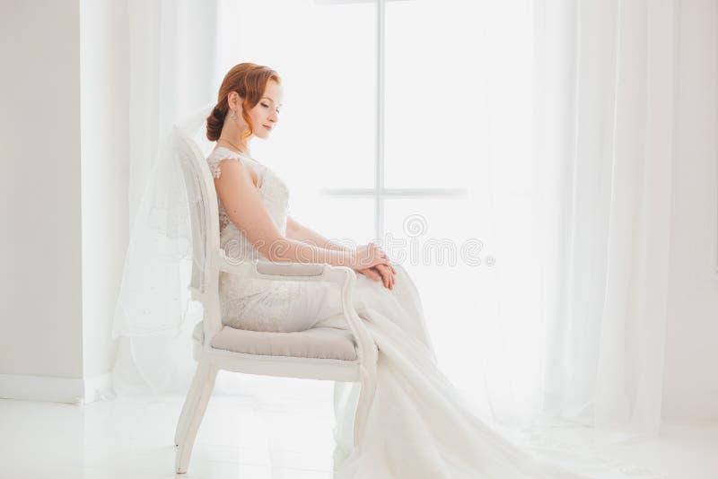 Jeune mariée modeste s'asseyant sur une chaise photographie stock