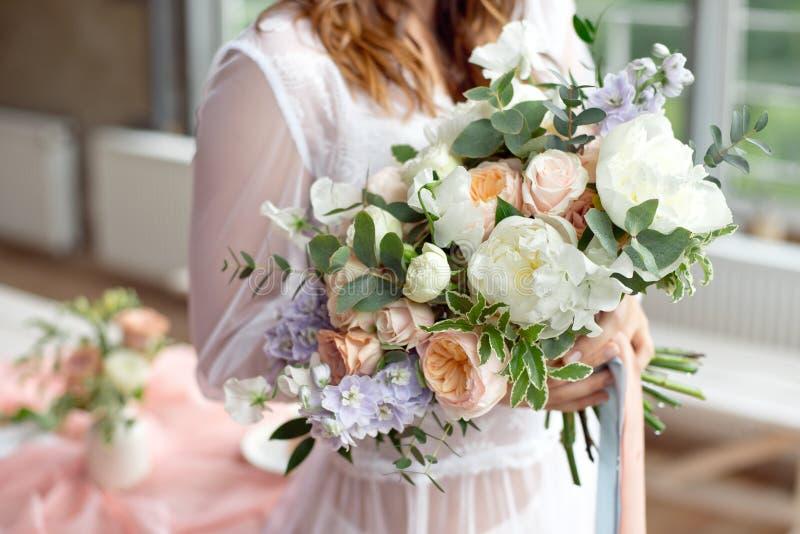Jeune mariée montrant à son beau bouquet de fleurs de boho les magazines chics de mariage de boho et les sites Web, bohémien, mod photographie stock
