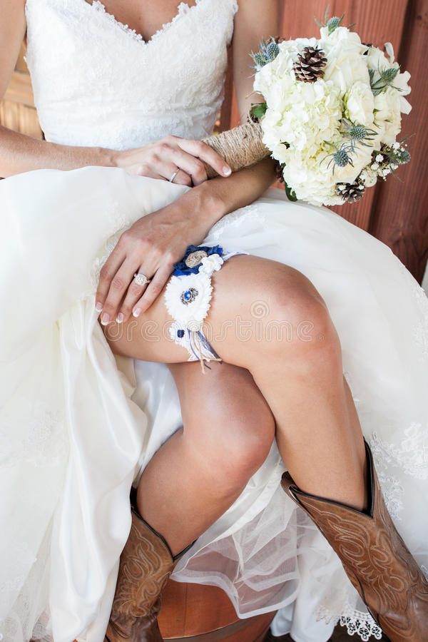 Jeune mariée montrant ses bottes de cowboy et jarretière et bouquet photographie stock libre de droits