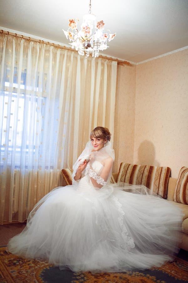 Jeune mariée par la fenêtre photo stock
