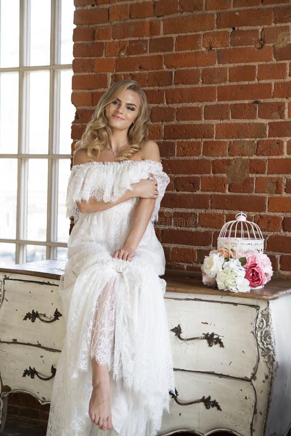 Jeune mariée posant se reposer sur la raboteuse de vintage photo stock