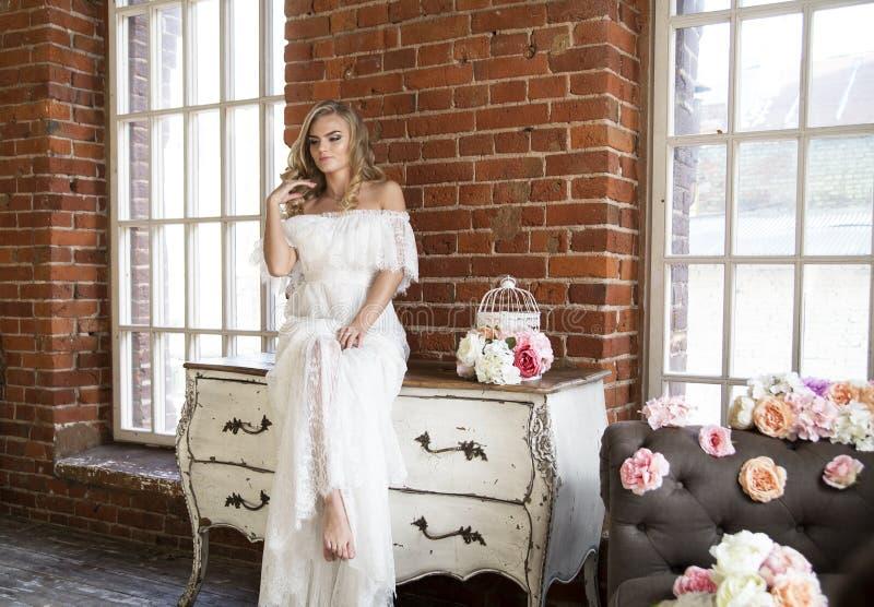 Jeune mariée posant se reposer sur la raboteuse de vintage photographie stock