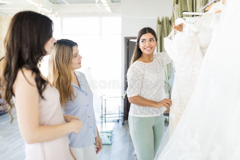 Jeune mariée pour montrer la robe de mariage aux amis photos stock