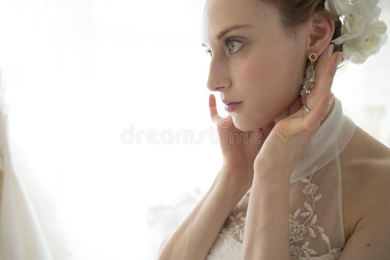 Jeune mariée pour s'assurer des boucles d'oreille photo stock