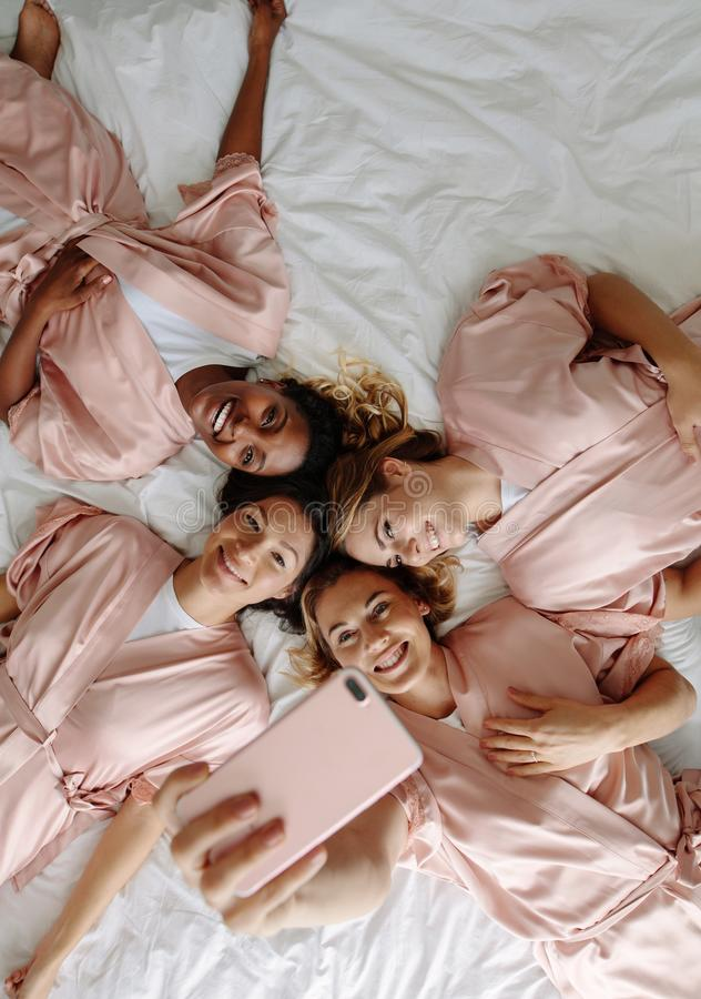 Jeune mariée prenant le selfie avec des demoiselles d'honneur tout en se trouvant sur le lit images libres de droits