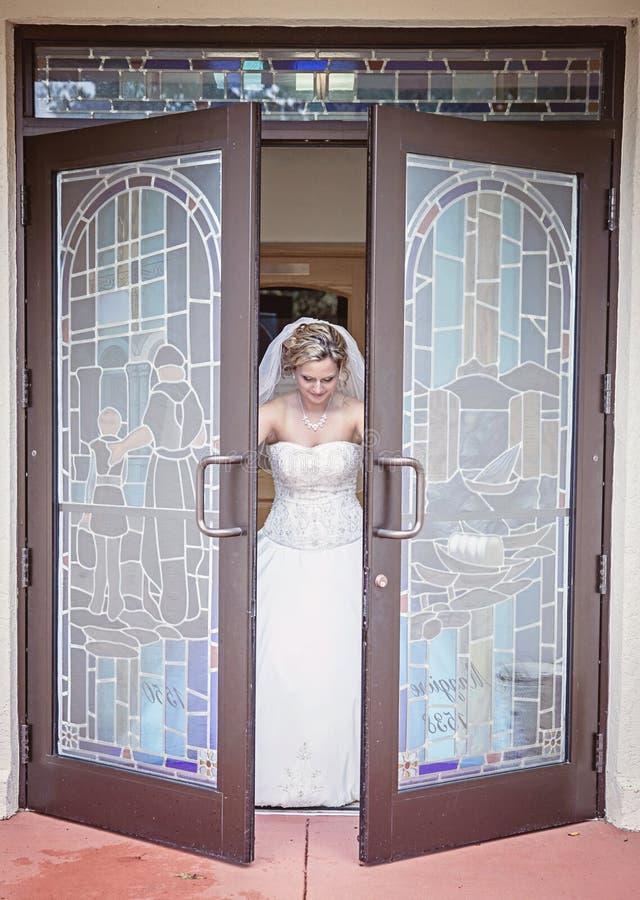 Jeune mariée quittant l'église image stock