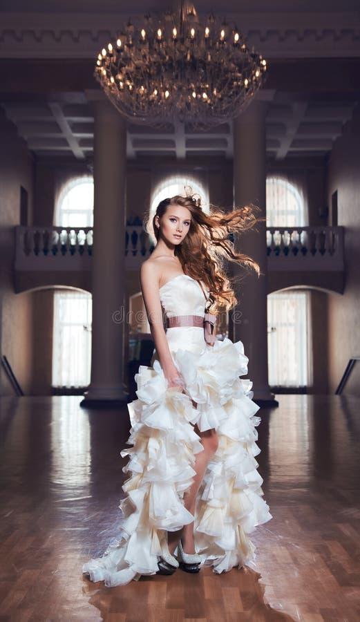 Jeune mariée rousse se tenant dans une belle salle images stock