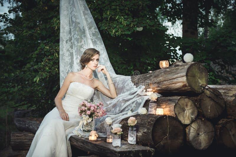 Jeune mariée s'asseyant d'une manière élégante sur la pile des rondins décorés photos libres de droits