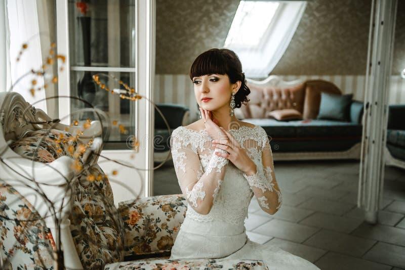 Jeune mariée s'asseyant sur un sofa dans une belle salle photographie stock