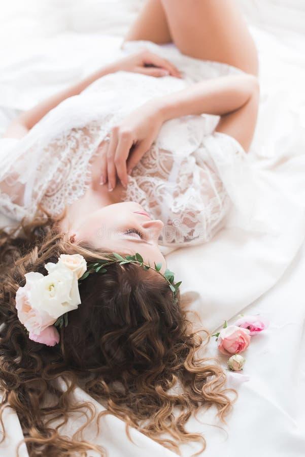 Jeune mariée se situant dans un peignoir blanc image stock