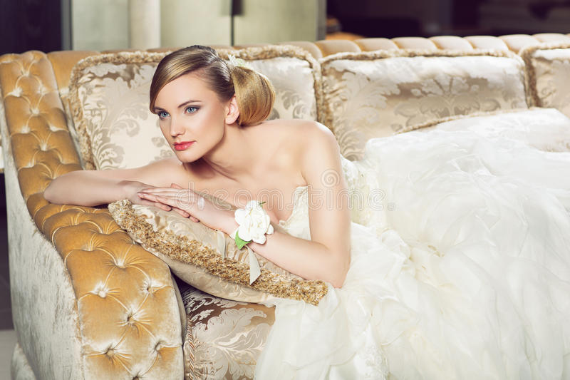 Jeune mariée se trouvant sur le sofa photographie stock