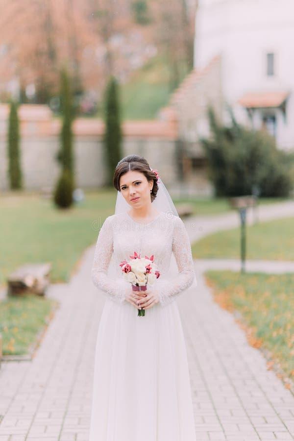 Jeune mariée sensible innocente tenant le bouquet nuptiale tandis que poses sur la ruelle de parc au jour ensoleillé image stock