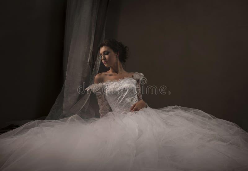 Jeune mariée sexy de brune assise dans sa robe de mariage blanche photo libre de droits