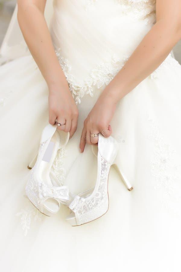 Jeune mariée tenant des chaussures de mariage photo libre de droits