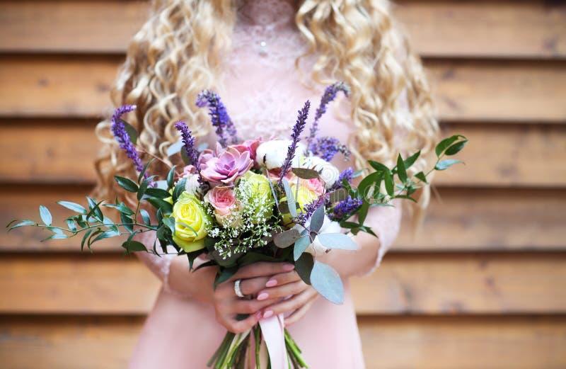 Jeune mariée tenant le bouquet de mariage avec les fleurs succulentes photographie stock