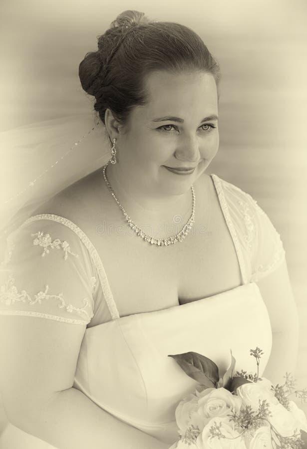 Jeune mariée tenant le bouquet en noir et blanc photographie stock libre de droits