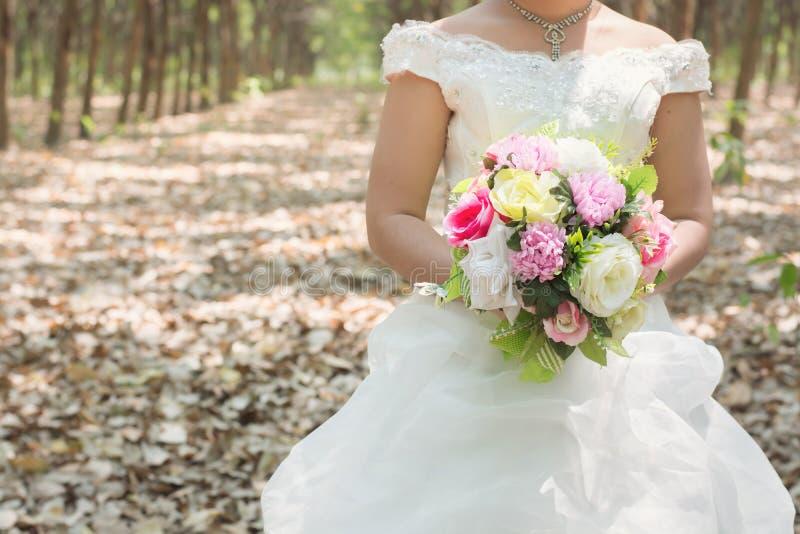Jeune mariée tenant le grand bouquet de mariage dans la forêt photos stock