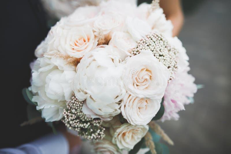 Jeune mariée tenant le grand et beau bouquet de mariage avec des fleurs image stock