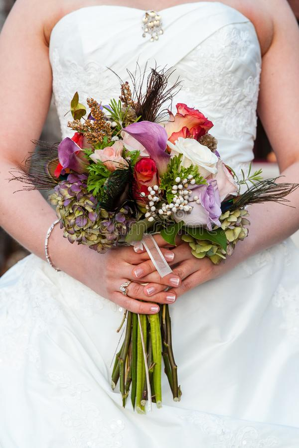 Jeune mariée tenant son bouquet l'épousant avec les fleurs pourpres, rouges, et blanches photographie stock