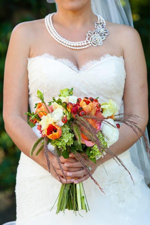 Jeune mariée tenant son bouquet l'épousant des fleurs avec les fleurs vertes, rouges, blanches, et oranges photographie stock