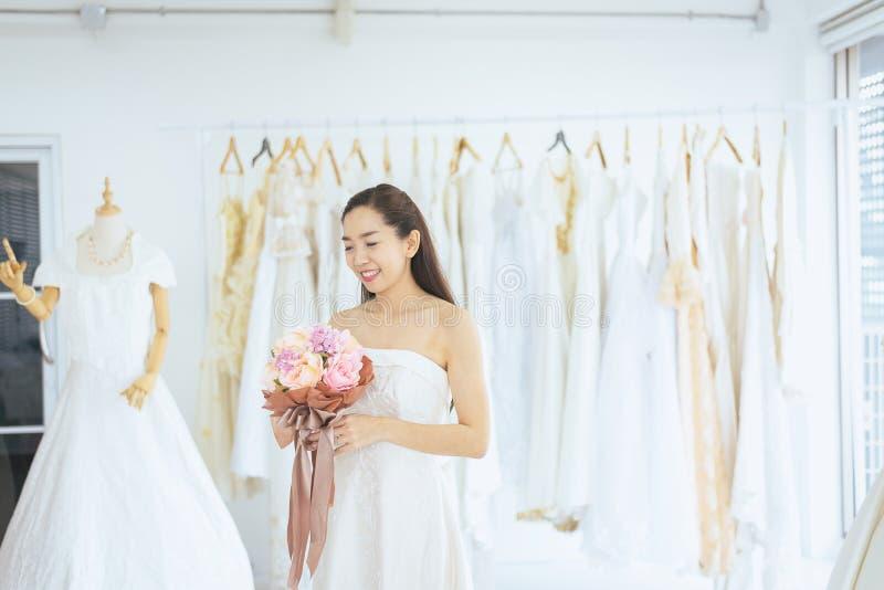 Jeune mariée tenant un bouquet en main pour l'instant souriant et heureux, romantique et doux de femme asiatique l'épousant et be images libres de droits