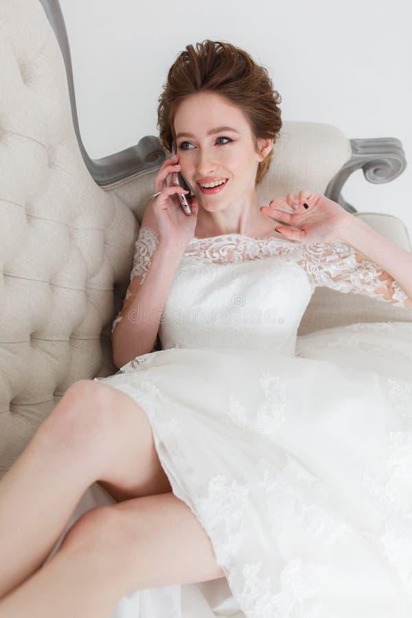 Jeune mariée tendre parlant au-dessus du téléphone portable se trouvant sur le divan photographie stock