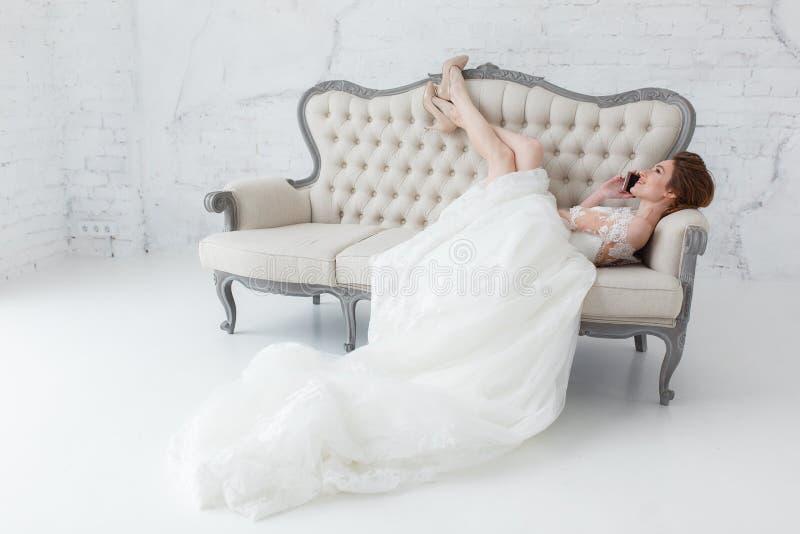 Jeune mariée tendre parlant au-dessus du téléphone portable se trouvant sur le sofa classique images libres de droits