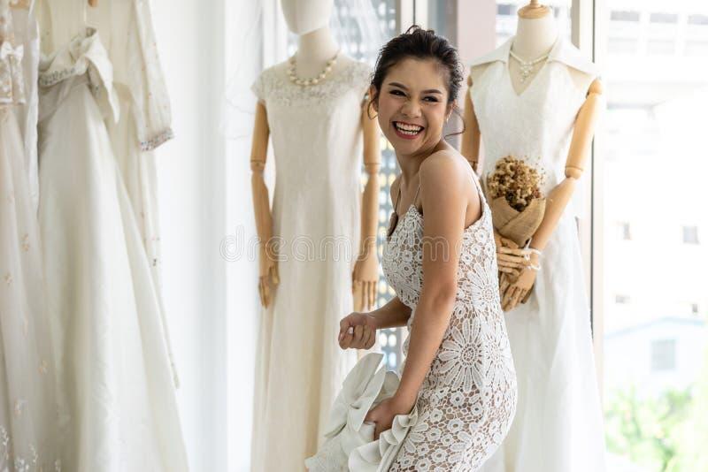 Jeune mariée thaïlandaise heureuse en épousant des boutiques de robes photographie stock