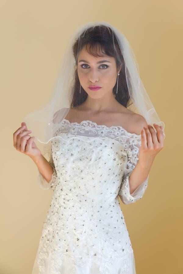 Jeune mariée traditionnelle posant avec le voile photographie stock libre de droits