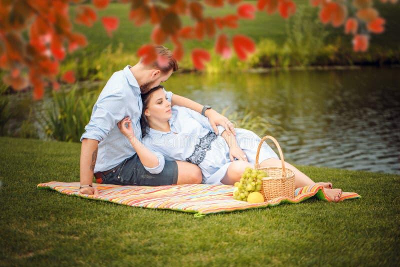 Jeune mari joyeux heureux de famille et son épouse enceinte ayant l'amusement ensemble dehors, au pique-nique dans le parc d'été photos stock