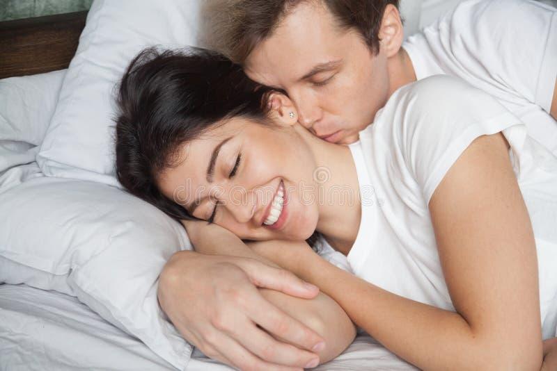 Jeune mari réveillant l'épouse l'embrassant et étreignant photo libre de droits