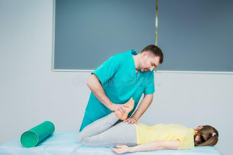 Jeune massage de réception femelle du chiroprakteur du thérapeute A étirant sa jambe patiente du ` s dans le bureau médical Médic photo libre de droits