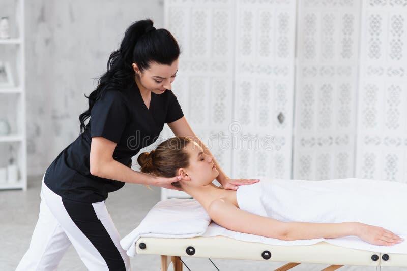 Jeune masseur professionnel faisant le massage pour la femme caucasienne somnolente sur le fond de pièce blanche images libres de droits