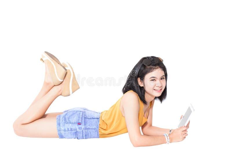 jeune mensonge et sourire de fille utilisant le PC de comprimé photo libre de droits