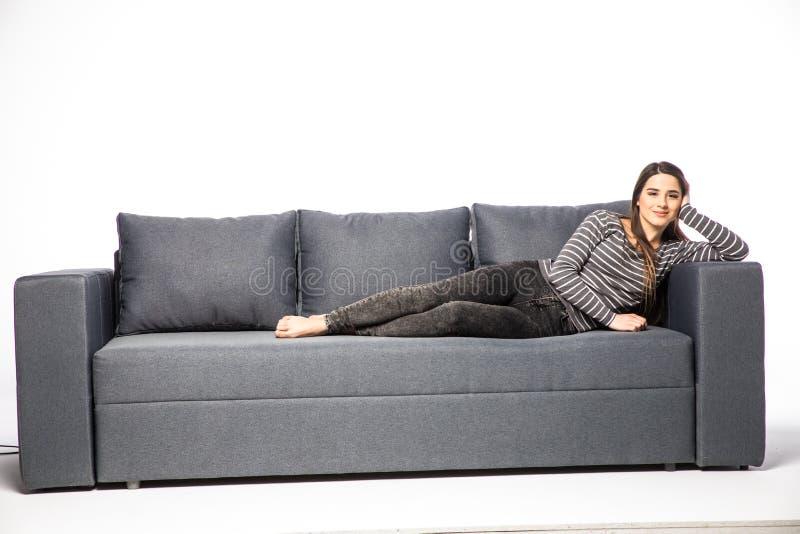 Jeune mensonge femelle sur un sofa d'isolement sur le fond blanc photographie stock