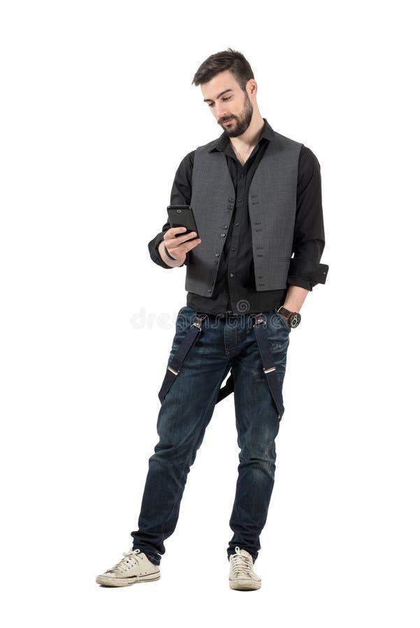 Jeune message à la mode de lecture d'homme sur son téléphone portable image stock