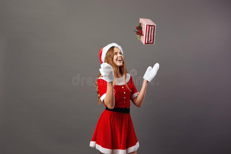 Jeune Mme avec du charme Claus s'est habillé dans la robe longue rouge, le chapeau de Santa et les gants blancs jette un cadeau d images stock