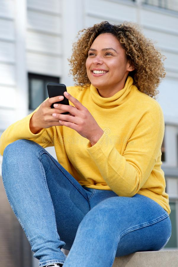 Jeune mobile attrayant de participation de femme d'afro-américain dans la ville images stock