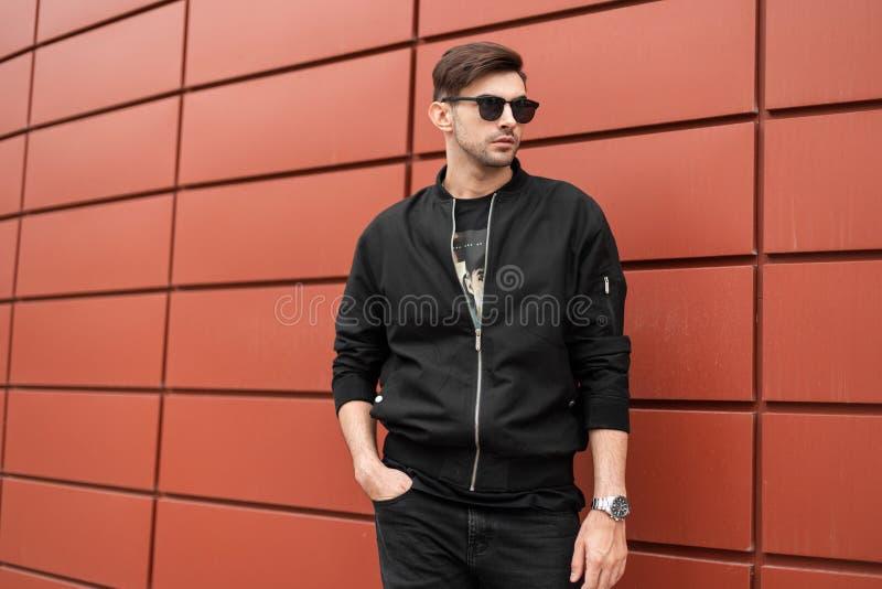 Jeune modèle élégant moderne d'homme dans la veste noire à la mode dans des lunettes de soleil de cru dans des jeans avec une pos photos stock