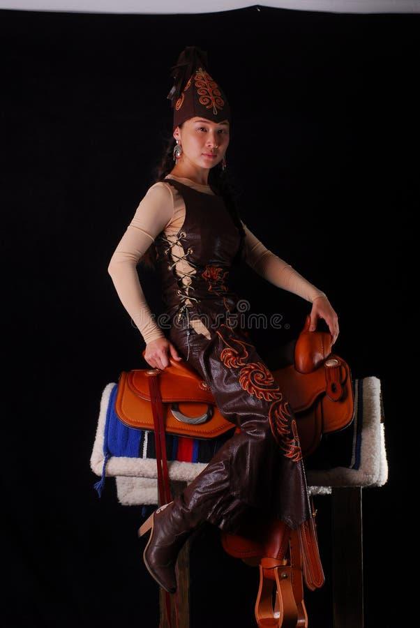 Jeune modèle asiatique dans des vêtements nationaux des nomades dans la selle possing dans le studio photo stock